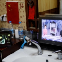 A screen showing a news report on the 2020 U.S. presidential election is seen next to a Chinese national flag at the Jin Ban Cun barbershop in Beijing on Sunday. | REUTERS