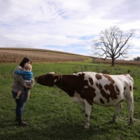 Rebecca Seidel and her son Adlai Seidel-Semsick greet a cow at their farm in Womelsdorf, Pennsylvania, on Oct. 27.  | REUTERS
