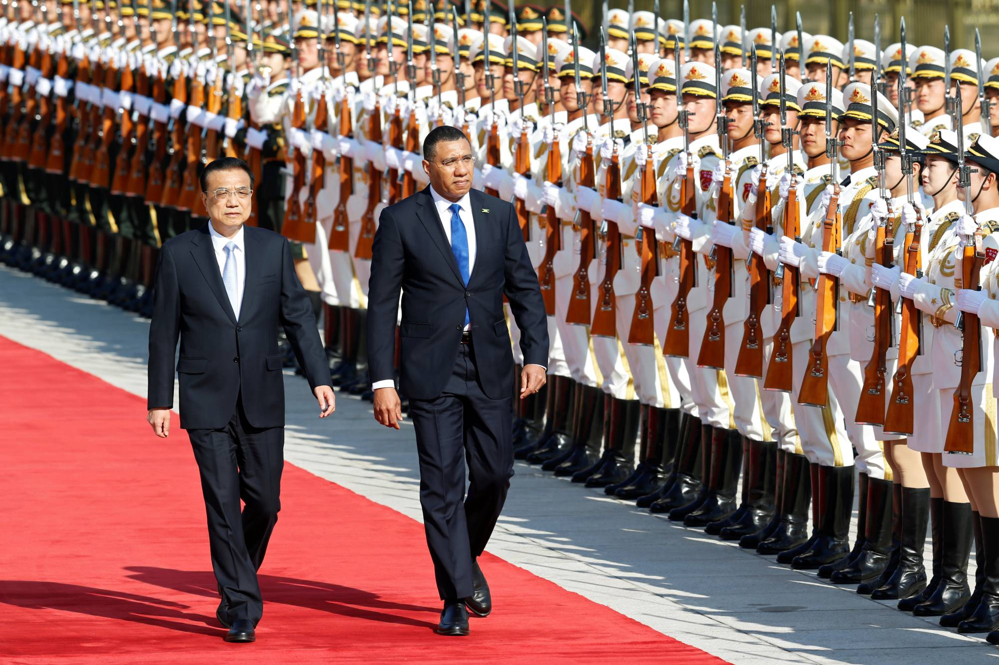 Jamaican Prime Minister Andrew Holness reviews the honor guard during a welcome ceremony with Chinese Premier Li Keqiang outside the Great Hall of the People in Beijing in November 2019.  | REUTERS