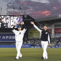 The Marines' Yudai Fujioka (left) and Yuki Karakawa wave to fans after their win over the Lions in Chiba on Sunday. | KYODO