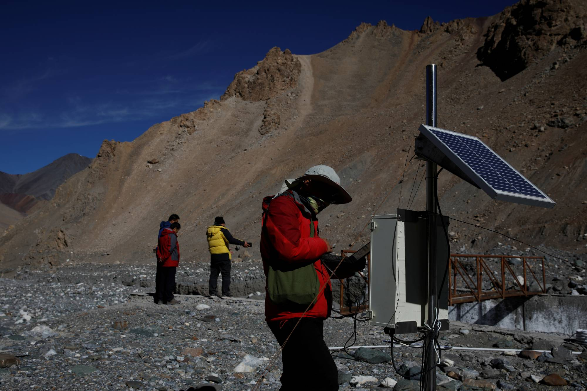 Jin Zizhen checks a data collection station next to a glacial stream of meltwater from the Laohugou No. 12 glacier. | REUTERS