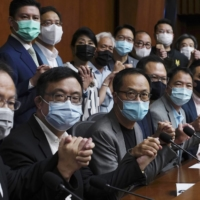 Pro-democracy lawmakers in Hong Kong pose before a news conference at the Legislative Council on Monday.  | AP
