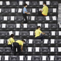 Staff sanitize seats at Takasaki Arena in Gunma Prefecture, where the All-Japan senior artistic gymnastics championships was held, in September. | KYODO