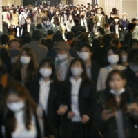 People walk in Osaka's Umeda district on Tuesday. In the past week, an abrupt increase in infections has been seen in Osaka, Nagoya, Aichi and Kanagawa prefectures. | KYODO