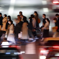 People walk in the city of Osaka's Umeda district on Tuesday. In the past week, an abrupt increase in infections has been seen in Osaka, Nagoya, Aichi and Kanagawa prefectures.   KYODO
