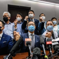 Pro-democracy lawmakers join hands at the start of a news conference at a Legislative Council office in Hong Kong on Wednesday. | AFP-JIJI