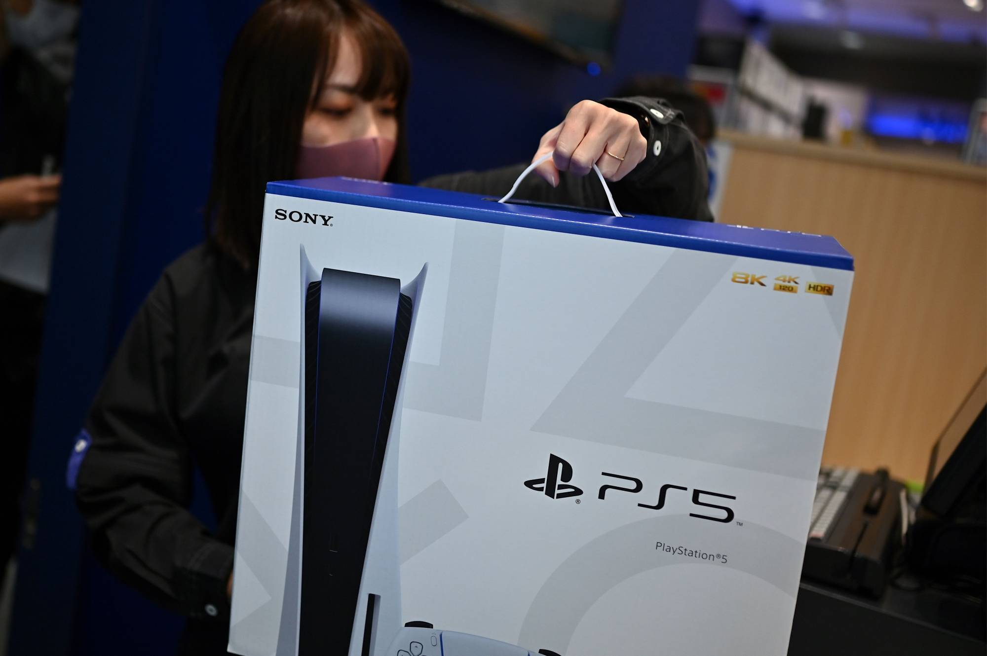 An employee prepares the new Sony PlayStation 5 gaming console for a customer on the first day of its launch, at an electronics shop in Kawasaki on Thursday. | AFP-JIJI