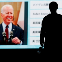 A large screen shows reports on Joe Biden's U.S. presidential election victory in Tokyo on Sunday. | REUTERS