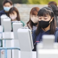 Visitors have their temperatures taken on Sunday before they enter Yoyogi National Gymnasium for an international gymnastics competition. | KYODO