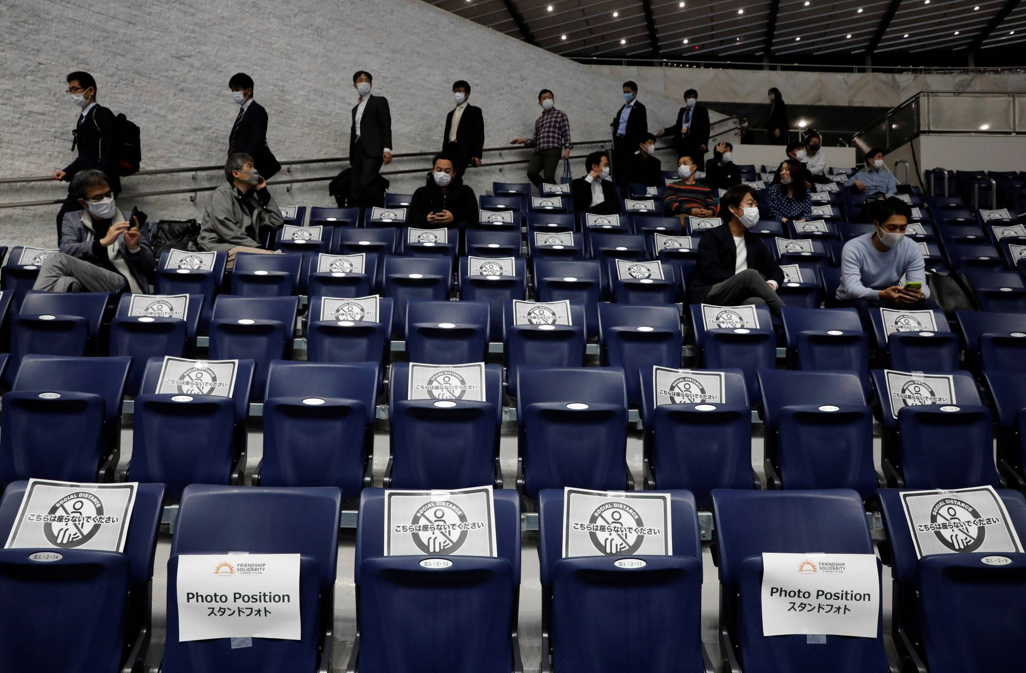 Signs to ensure social distancing are placed on media members' seats ahead of the Friendship and Solidarity Competition, a gymnastics event held Sunday in Tokyo. | REUTERS