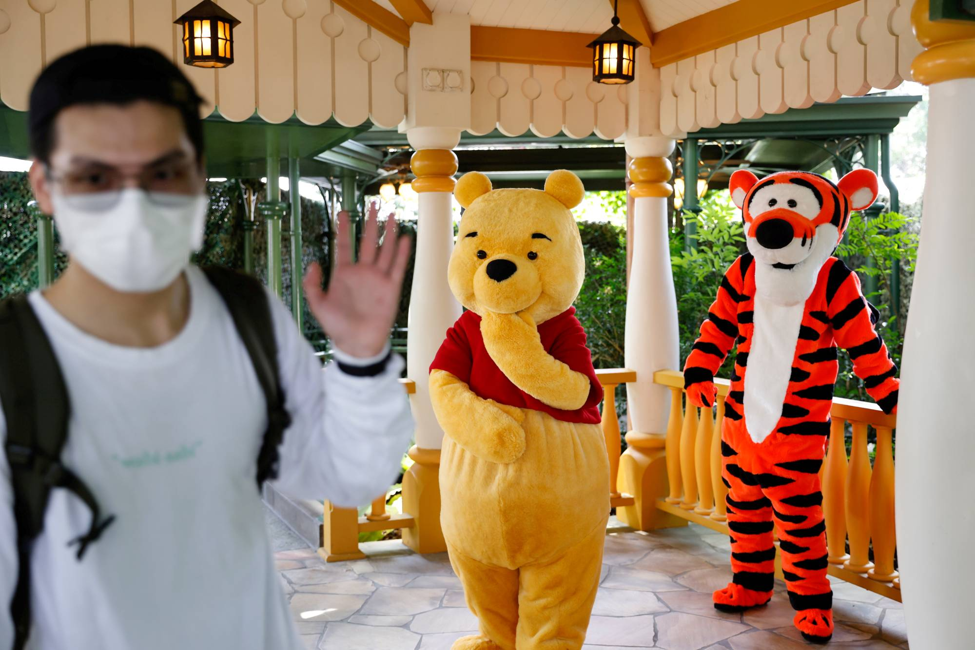 A visitor greets Disney characters during the reopening of Disneyland to the public, after a second closure due to COVID-19, in Hong Kong on Sept. 25. | REUTERS
