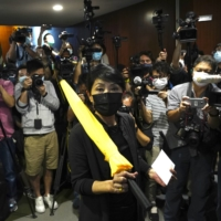 Pro-democracy legislator Claudia Mo (center) poses for photographers before handing in her resignation letters at the Legislative Council in Hong Kong on Thursday. | AP