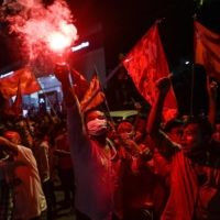 Supporters of the National League for Democracy party celebrate in front of the party's headquarters in Yangon on Tuesday. | AFP-JIJI