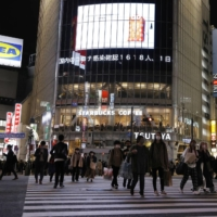 People walk on a crossing near Shibuya Station Thursday as a large screen shows a news of the number of COVID-19 cases confirmed in Japan on the day hitting a record high.   KYODO