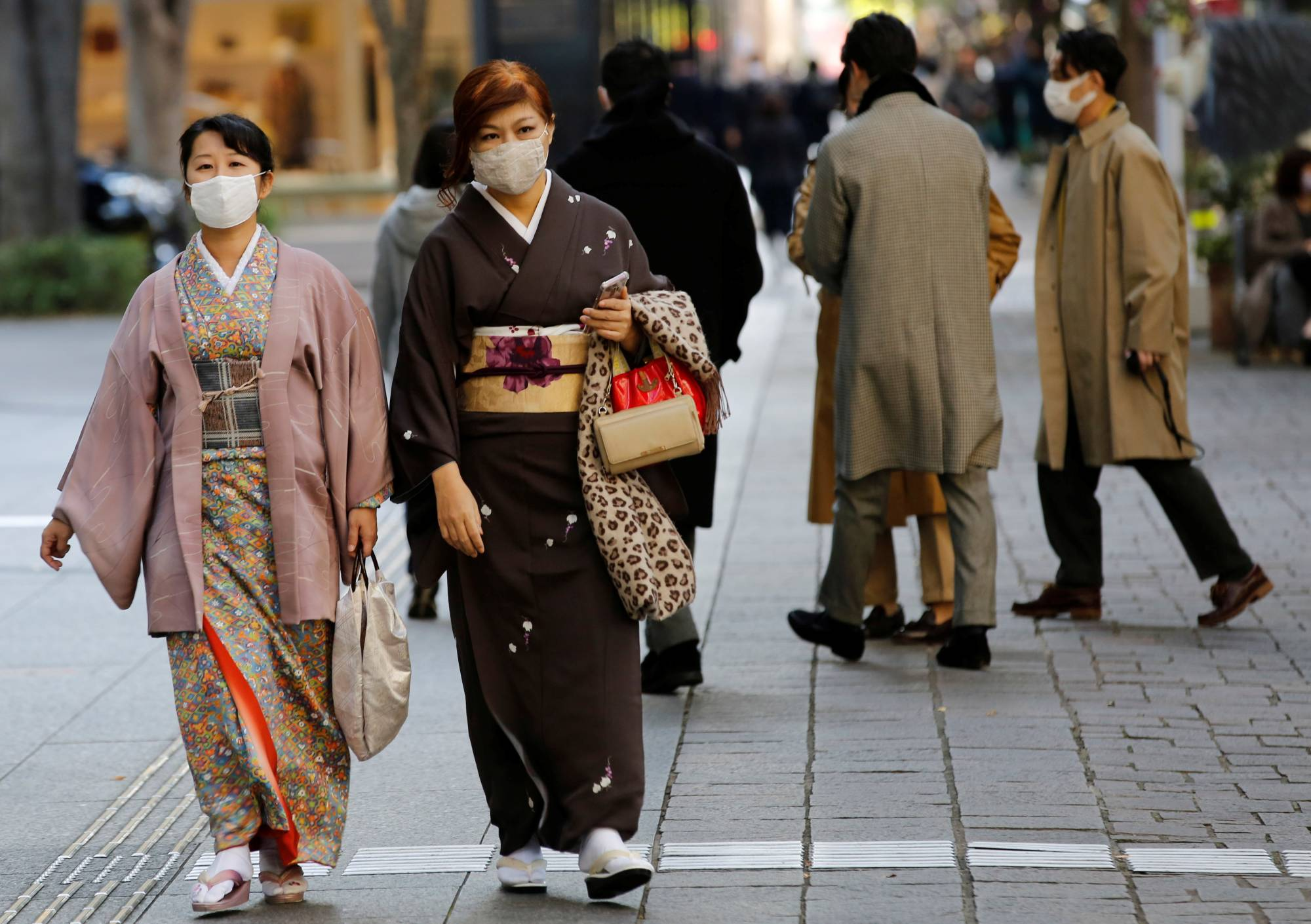 Women wearing kimono and masks walk in Tokyo on Friday. | REUTERS