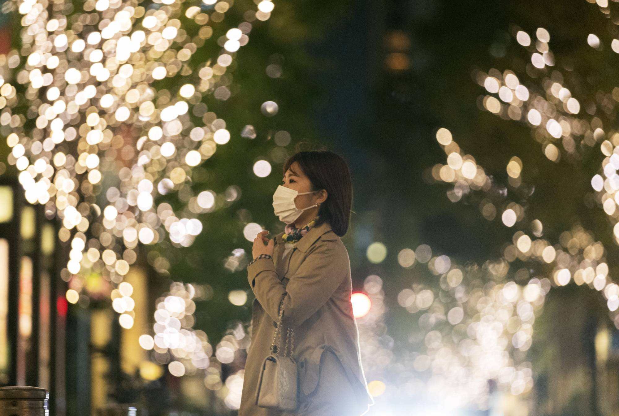 A woman walks down a street decorated with seasonal lighting in Tokyo on Thursday. | AP