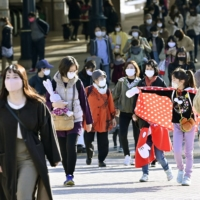 A crowd approaches Tokyo Disneyland in Chiba Prefecture on Saturday. | KYODO