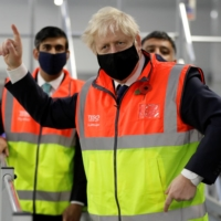 British Prime Minister Boris Johnson visits a tesco.com distribution center in London on Wednesday. | POOL / VIA REUTERS