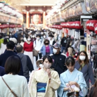 People walk on the crowded Nakamise shopping street in Tokyo's Asakusa district on Friday. | KYODO