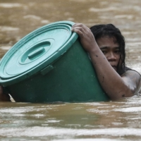A man uses a plastic canister to float while negotiating rising floodwaters from Typhoon Vamco in Marikina, Philippines, on Thursday.  | AP