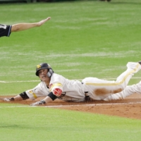 Hawks catcher Takuya Kai slides into first base as the tiebreaking run scores with two outs in the eighth inning during Game 1 of the PL Climax Series on Saturday in Fukuoka.  | KYODO