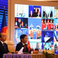 Vietnam's Prime Minister Nguyen Xuan Phuc (left) and Minister of Industry and Trade Tran Tuan Anh attend the online signing ceremony for the Regional Comprehensive Economic Partnership (RCEP) trade pact, in Hanoi on Sunday. | AFP-JIJI