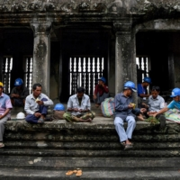 Gardeners rest after climbing down from the exterior of the Angkor Wat temple. | AFP-JIJI