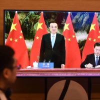Chinese Premier Li Keqiang (center) looks on as Minister of Commerce Zhong Shan signs the agreement, as seen on a TV monitor, during the signing ceremony for the Regional Comprehensive Economic Partnership (RCEP) trade pact during an online ASEAN summit on Sunday. | AFP-JIJI