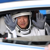 Crew-1 mission astronaut Soichi Noguchi greets onlookers during the crew walkout at the Neil A. Armstrong Operations and Checkout Building en route to launch complex 39A at the Kennedy Space Center in Florida on Sunday. | AFP-JIJI