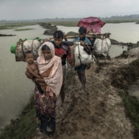 Rohingya refugees make their way through a downpour after crossing the Naf River from Myanmar into Bangladesh, near the village of Palong Khali, in September 2017.  | ADAM DEAN / THE NEW YORK TIMES