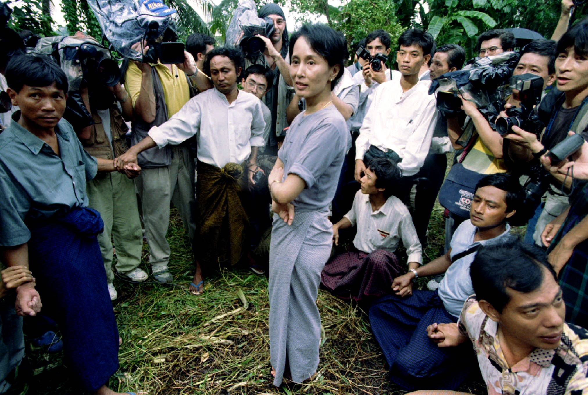 Aung San Suu Kyi is surrounded by security guards and journalists as she walks out of her house in Rangoon in July 1995. | REUTERS