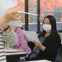 Raquel Garcia, a third generation Japanese-Filipino who lost her job at a factory in Mie Prefecture earlier this month, studies Japanese at a labor union gathering on Nov. 11 in Matsusaka. | CHUNICHI SHIMBUN