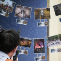 A photographer looks at pictures depicting the 2019 campus siege at the height of the city's pro-democracy protests at an exhibition in the Chinese University of Hong Kong on Saturday. | AFP-JIJI