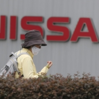 A woman walks past the corporate logo at Nissan Motor Co.'s global headquarters in Yokohama in May. | AP