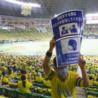 A volunteer holds up a sign reminding fans to follow infection prevention measures as the Hawks' PayPay Dome admits a crowd of over 10,000 for the first time since the start of the pandemic on Sept. 19 in Fukuoka. | KYODO
