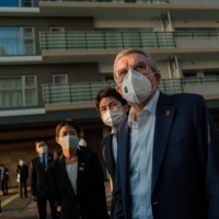 IOC President Thomas Bach talks to journalists while visiting the Tokyo 2020 athletes' village on Tuesday. | POOL / VIA AFP-JIJI