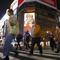 People walk in the Susukino entertainment district of Sapporo this month. The central government has pledged to financially support shops and restaurants that are asked to shorten their business hours as coronavirus cases surge nationwide. | KYODO