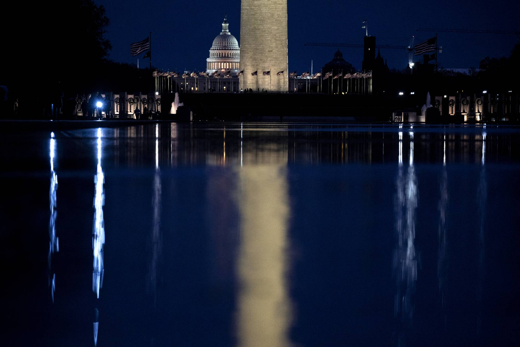The dome of the U.S. Capitol rises behind the Washington Monument in Washington. Lobbyists and other advisers who help clients navigate Washington are quietly highlighting ties to President-elect Joe Biden and his team in pitches to prospective clients.  | STEFANI REYNOLDS / THE NEW YORK TIMES