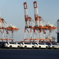 Sports utility vehicles bound for shipment are seen at a port in Yokohama in October. The rate of decline in Japan's exports slowed in October to just below the levels seen before the novel coronavirus pandemic, helped by expanding demand in the United States and China. | BLOOMBERG