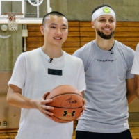 Keisei Tominaga stands with Warriors guard Stephen Curry during an event in Tokyo in 2019. | KAZ NAGATSUKA