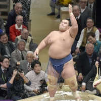 Kotoshogiku throws salt in the air prior to a bout at the New Year Grand Sumo Tournament in 2016. | KYODO