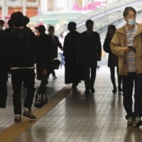 People walk through an underpass in Tokyo on Wednesday. | AP