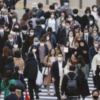 People walk in Tokyo's Shinjuku district Wednesday as the number of confirmed daily COVID-19 cases in the capital hit a new high. | KYODO