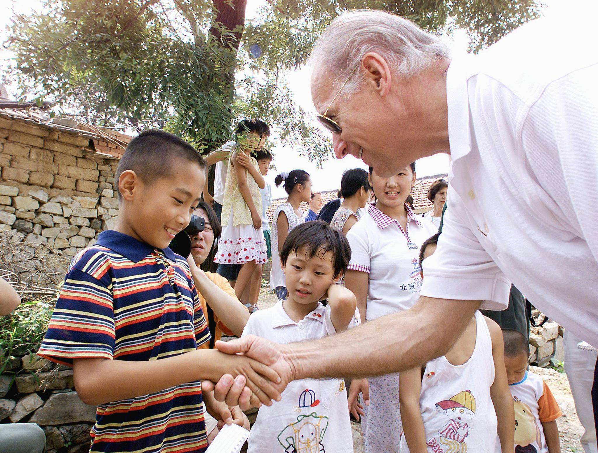 Then-Sen. Joe Biden shakes hands with 9-year-old Gao Shan, the boy Biden proclaimed as the future president of China, during a visit to the village of Yanzikou, north of Beijing, in August 2001. | POOL / VIA AFP-JIJI