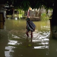 A resident wades through floodwater in Isabela, in the northern Philippines, on Tuesday. | JES AZNAR / THE NEW YORK TIMES