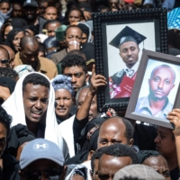 Mourners carry portraits of victims of the 2019 Ethiopian Airlines crash during a mass funeral at Holy Trinity Cathedral in Addis Ababa, Ethiopia, on March 17, 2019.  | AFP-JIJI