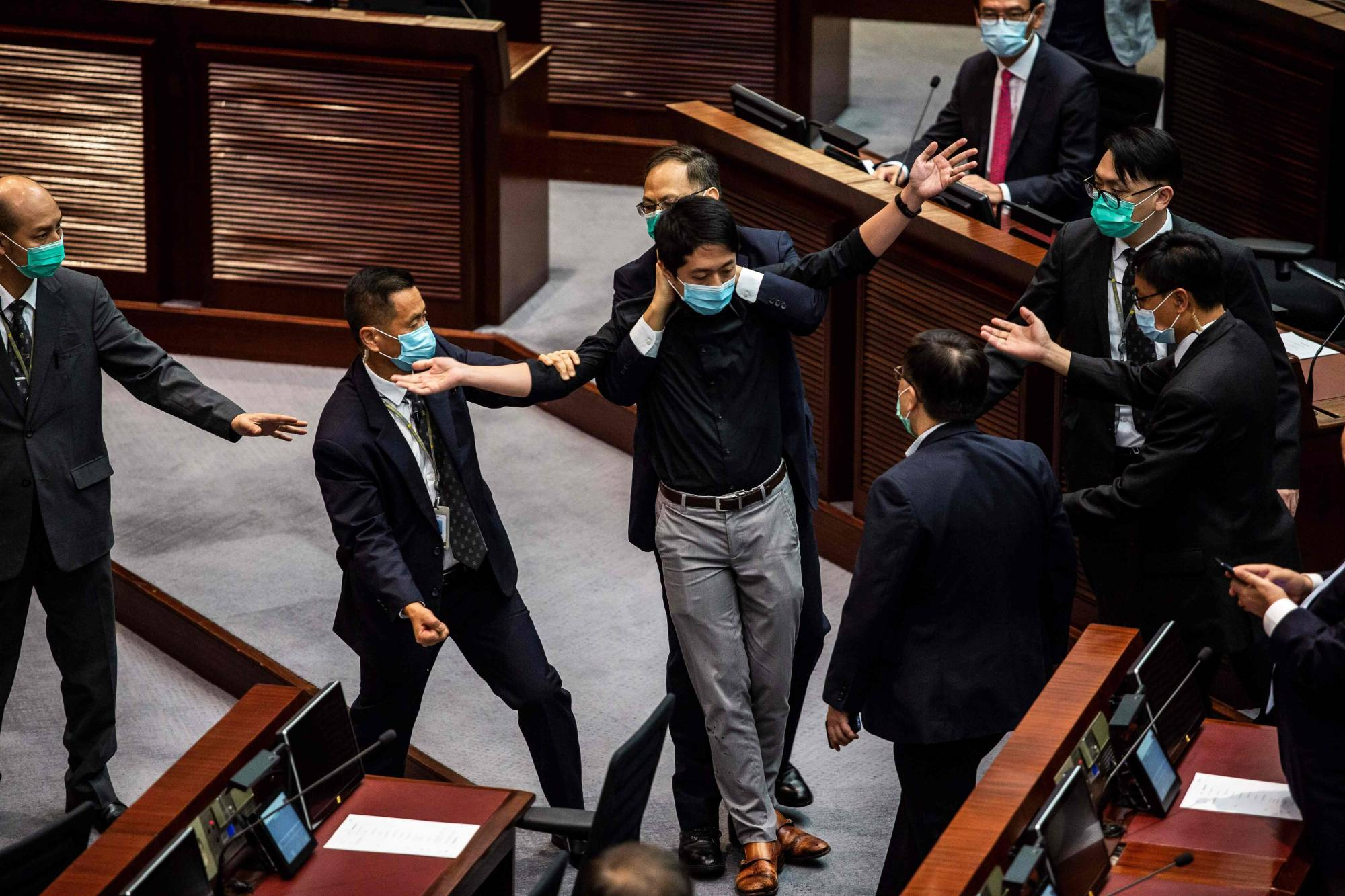 Pro-democracy legislator Ted Hui is removed by security guards after throwing a jar containing a foul-smelling liquid onto the floor during a June Legislative Council debate on a law that bans insulting China's national anthem.    AFP-JIJI