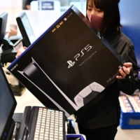 An employee prepares a new Sony PlayStation 5 gaming console for a customer on the first day of its launch on Nov. 12 at an electronics shop in Kawasaki. | AFP-JIJI
