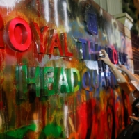 Demonstrators spray-paint a plaque in front of the police headquarters during a rally in Bangkok on Wednesday.  | REUTERS