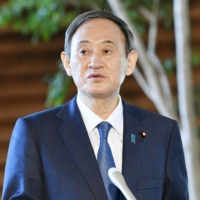 Prime Minister Yoshihide Suga, speaking Thursday at the Prime Minister's Office, urges people to wear masks and maintain social distancing. | KYODO